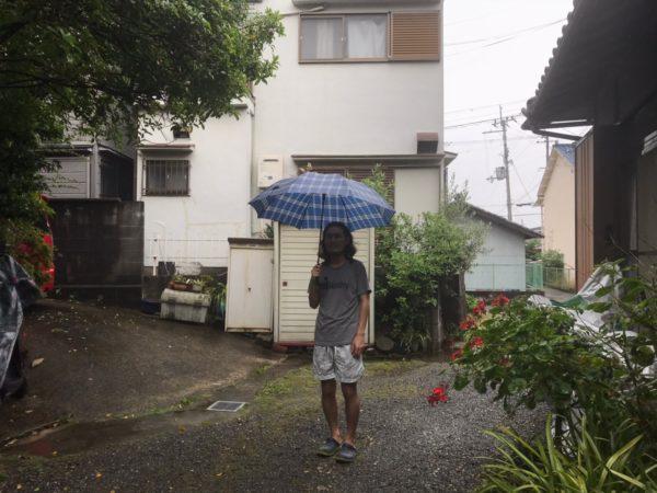 傘を差して立ち尽くす